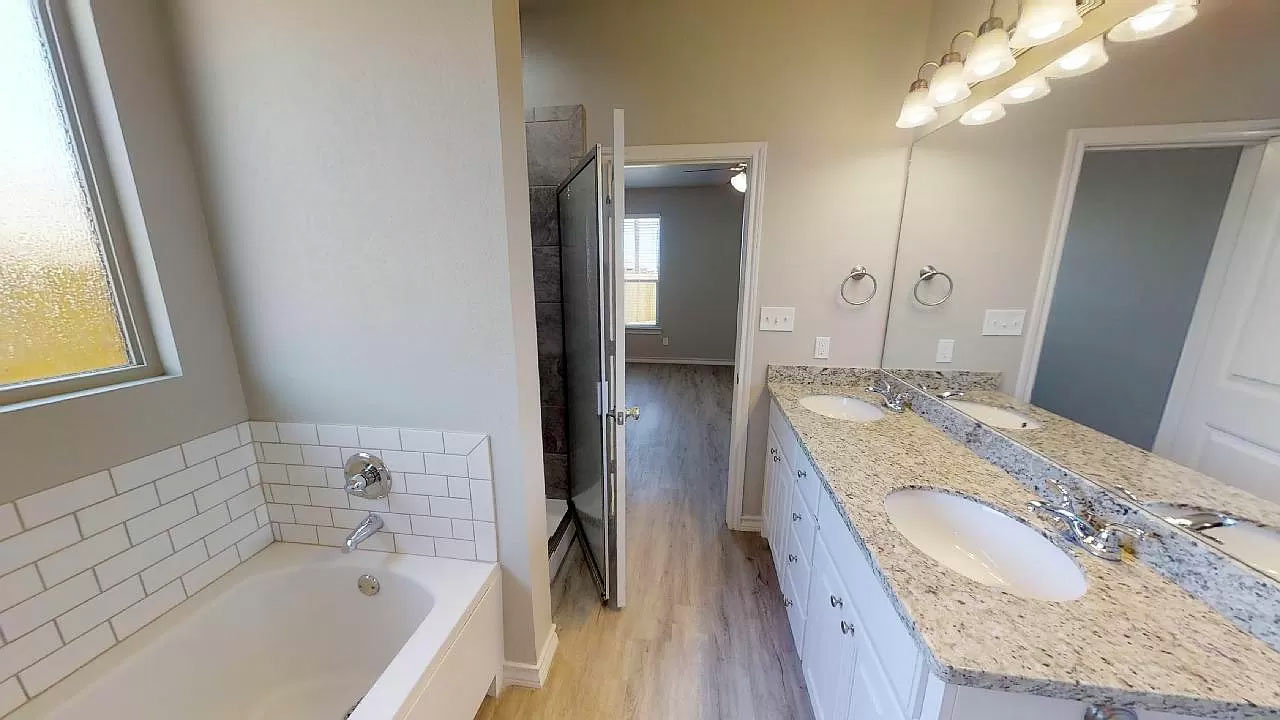 Bathroom with tub and granite counters in New Home in Lubbock TX